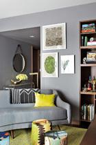 """""""我总是在玩各种调调的灰色,这种方式能让房间与房间之间柔和过渡,呈现无缝对接。""""起居室一角,墙上的三幅画作出自艺术家Klien Reid。"""