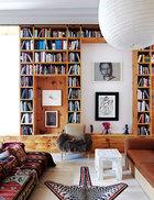客厅中通高的松木书架是主人夫妇的收藏品,木纹石膏小桌由John Dickinson设计。三色滚边的古董美洲豹皮毯是Daniel Sachs的设计。