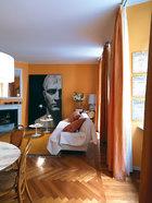 """温暖的色彩能驱赶米兰城内常见的阴郁,立在地上的黑白""""名画""""竟是用Bisazza自家的马赛克拼贴而成。客厅与用餐区开放相连,这里摆着圆形的大理石桌子。在左边有Thonet的木椅子,Santa & Cole的吊灯;在后面,两个圆形的咖啡桌由Eero Saarinen为Alivar设计,古董壁炉、镜子和由玻璃马赛克拼贴成的大型装饰板Bonaparte均由Carlo Dal Bianco为Bisazza设计。在右侧,靠近窗帘的地方挂着斯卡拉剧院的节目单。"""