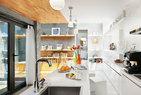 白色的开放式厨房不仅是餐厨空间,还是宝姐看书、工作的地方。白色的开放式厨房里,岛台上装橙子的水果盘、架子上的木色碗盘和金色台灯均来自UCCA,而 岛台上黄色和橘色的花瓶,以及架子上白色可组合茶具摆件则来自+86。开放式厨房的一旁是兼具储物与展示功能的壁架,壁架上的黄色小座钟、绿色自行车插片 摆件,以及架子顶层的白色树形插片摆件均来自BoConcept 北欧风情。