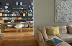 从客厅看向更深处的书房兼茶室,近处墙面上的画作是岳敏君创作的综合材料作品《迷宫》,书房的长桌为定制品,几把不同款式的Eames椅混搭在桌旁,墙上的搁架也由Arnd为这个家量身定制。