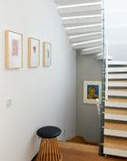 楼梯间,近处墙面上的三幅小画来自德国艺术家伊门多夫,楼梯下挂着一幅艺术家王广义的作品。