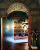 """贝里尼的书房内,由Norman Foster设计的""""Nomos""""全玻璃书桌搭配艺术装饰风格的圈手椅,后面是Mario Broglio1930年代的作品《La Lettura》。"""