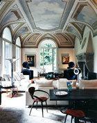 """面朝户外的起居室中,穹顶上1930年代风格的湿壁画俯视着两张""""乔治""""沙发,由意大利B & B公司的Citterio设计。"""
