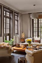 """""""很多家具背后都隐藏着有趣的故事,我愿意为好故事买单。""""客厅沙发区,左面的窗正对入户的天井。花瓶中郁金香与黄绿柠檬的新鲜组合是主人的得意之作。"""