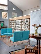 """新近增建的起居室,整面墙展示的都是萨洋收藏的温酒器和酒壶, """"等将来老了,我要研究那些酒壶的文化。""""新起居室是改造加建的主要部分,有一面墙高的架子上摆放着萨洋收藏的温酒器和茶壶,四把蓝色的椅子原来属于罗马尼亚驻华使馆,他们在二手店淘回来的,凳子上摆的书就是萨洋最近出版的GreatWall Style 。空间里的镜子和窗户映照出不同的风景。"""