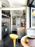 厨房十分宽敞,绝好的光线和窗外景色,一定留得住主人在这里消磨大把时光。厨房收拾得井然有序,灶台上方挂着各式各样的锅,里面架子上摆着一排英文美食书籍和一些瓷器。