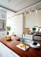 """Ceccotti Collezioni餐椅真是家具中的杰作,坐着它进餐,你就仿佛坐在云彩上!""餐厅中的巴西花梨木长桌一半用于就餐,一半成为了配餐台,百强家居进口的意大利Ceccotti Collezioni餐椅以其极轻的重量和优雅的外形成为了餐厅的一大亮点。餐桌上一排独特的圆锥体玻璃杯由沉重的瓷质底座固定,来自Spin商店。""我用它来喝香槟、茶和果汁,朋友们能因它们可爱的外形而多喝好几杯!""一排Arnd自己制作的玻璃瓶吊灯散发着轻巧柔和的光芒。家中大面积使用了由Casa Jolie引进的意大利 ListoneGiordano地板,远处墙上的海报中,写着荷兰语""生活是甜蜜的""。"