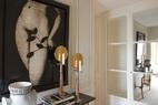 """门厅中醒目的女性胴体片""""Eve""""来自摄影师Colby Caldwell。玄关上的黑白色瓷花瓶""""Circa""""是1950年由RogerCapron创作的,旁边的两座烛台来自巴黎的AgnèsMonplaisir画廊。"""