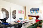 """阳光明媚的客厅, 画作及小配饰带来整体欢快的气氛,一切静暖和乐。一黑一白两张Chester古典沙发的一侧,立着Alexandre Arrechea的巨幅水彩画作品""""蝴蝶迷宫""""(Laberinto Mariposa),装裱在两只Plexiglás盒子中的""""血块""""(Coágulos)系列油画是Marion Theme的作品,以上画作都来自Casado Santapau画廊。沙发上的靠垫由William Wegman为Crypton品牌设计,大茶几上的假花来自The Flower Room。右侧角落中的Jingzi硅胶灯由Herzog & De Meuron为Belux设计,红色亮面立方体桌上摆着Seletti的陶瓷雕塑Vanitas。"""