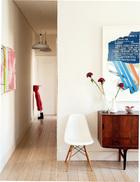 从客厅看向门口,近处摆放着EL 8的丹麦柜和由Vitra公司生产的Eames椅,走廊尽头的小红帽雕塑是Jorge Pineda的作品,购于Raquel Ponce美术馆,两只复古吊灯来自Vintage 4P。