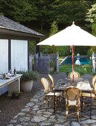 室外餐桌也对着泳池,这里正是观看远山的角度。花园里的栅栏门灵感来自马厩。