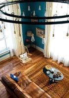 美丽的阳光与丰盛的茶点,让这个被冰天雪地包围的房子暖意融融。被抬高的客厅地面使得原先只是齐腰高的窗户变成了真正的落地窗,客厅的视野也由此变得更加开阔了。巨大的铸铁吊灯,是Blake和当地手作艺人共同劳动的成果,其中颇具怀旧感的灯泡及皮质大沙发、木质孔雀扶手椅皆购于淘宝。