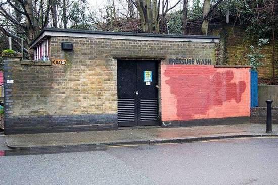 """清洁队员继续把位于红墙上的""""红漆""""二词盖掉,却唯独留下了砖墙上面""""水洗""""二词。"""